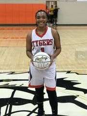 Mansfield Senior's Talayzha Catchings poses with a specially made basketball commemorating her 1,000th-career point on Saturday afternoon.