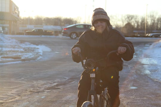 Maxwell Ulery rides his bike to work at the Wendy's on Delaware Avenue on Friday. There are no sidewalks or bike paths along parts of Delaware Avenue.