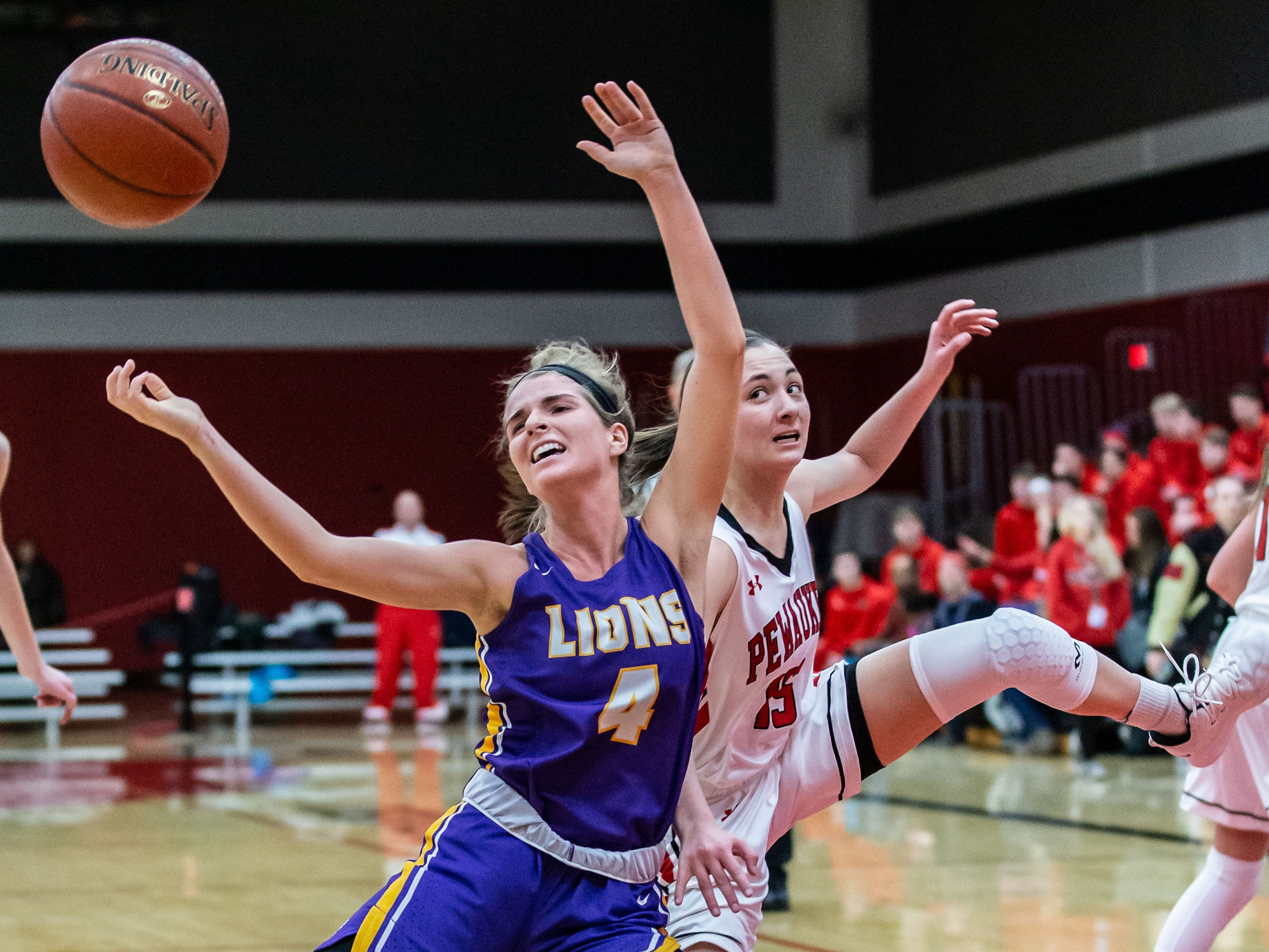 New Berlin Eisenhower's Julia Hintz (4) battles for possession under the hoop with Pewaukee's Kennedy Osterman (15) during the game at Pewaukee on Friday, Jan. 25, 2019.