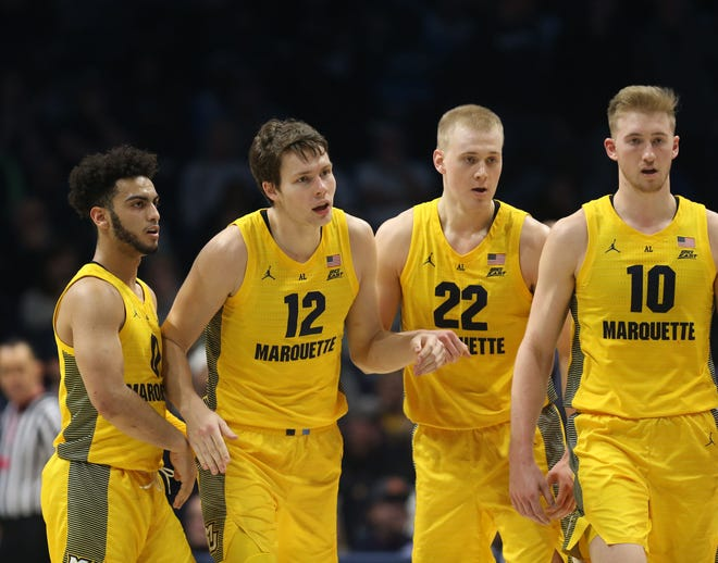 Marquette's  Markus Howard  (left) Matt Heldt,  Joey Hauser, and  Sam Hauser  huddle during the second half.