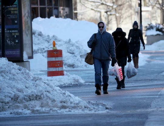 Pedestrians bundled against the cold cross East Kilbourn Avenue as they walk along North Water Street near the Marcus Center in Milwaukee on Friday.