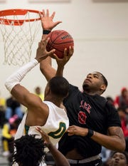 Carver forward Centarrio Hinson, left, is blocked by Lee forward Demond Robinson (0) at Carver High School in Montgomery, Ala., on Friday, Jan. 25, 2019. Lee defeated Carver 57-50.