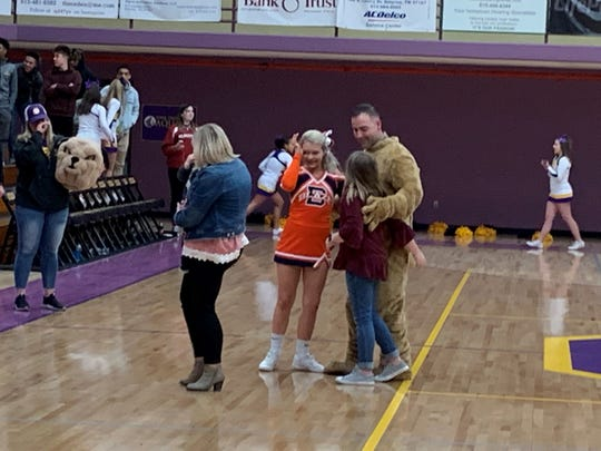 Air Force Tech Sgt. Ben Nelson is pictured with his daughters, including Blackman cheerleader Ashlynn Nelson, Friday at Smyrna. Ben Nelson dressed in a Bulldog mascot uniform to surprise his daughters after returning from deployment.