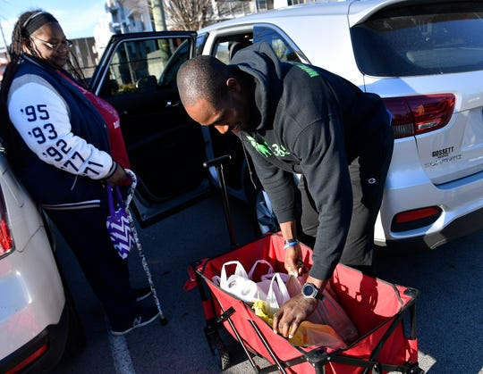 Catholic Charities volunteer Kempson Onadeko helps federal employee Lendia Rosser load groceries into her car at a food bank for furloughed federal employees Friday Jan. 25, 2019 in Nashville, Tenn.
