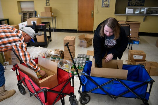 Catholic Charities volunteers Barry Jones and Rae Zehel load food boxes for furloughed federal employees Friday Jan. 25, 2019 in Nashville, Tenn.