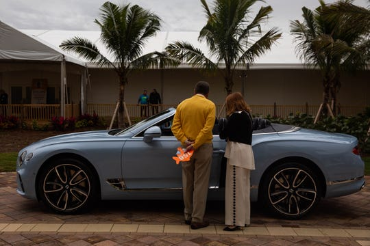 John and Georgia DallePazze inspect the 2020 Bentley Continential GT Convertible before the auction at the Naples Winter Wine Festival, held at the Ritz-Carlton Golf Resort on January 26, 2019.