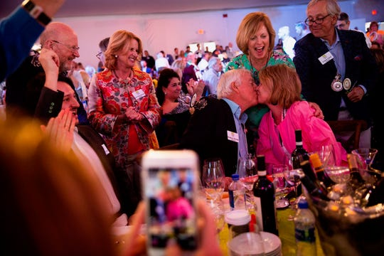 Rodney and Kathy Woods kiss after winning lot 23, a 10-night trip through Italy, during the Naples Winter Wine Festival at the Ritz-Carlton Golf Resort in Naples on Saturday, Jan. 26, 2019.
