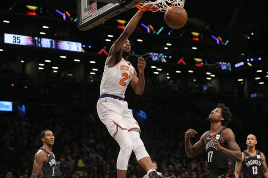 Jan 25, 2019; Brooklyn, NY, USA; New York Knicks center Mitchell Robinson (26) dunks against Brooklyn Nets small forward Rondae Hollis-Jefferson (24) and power forward Ed Davis (17) and point guard Shabazz Napier (13) during the second quarter at Barclays Center.
