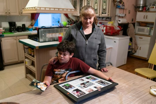 Ian Gaytan looks at family photos, comforted by grandmother Olga Gaytan.
