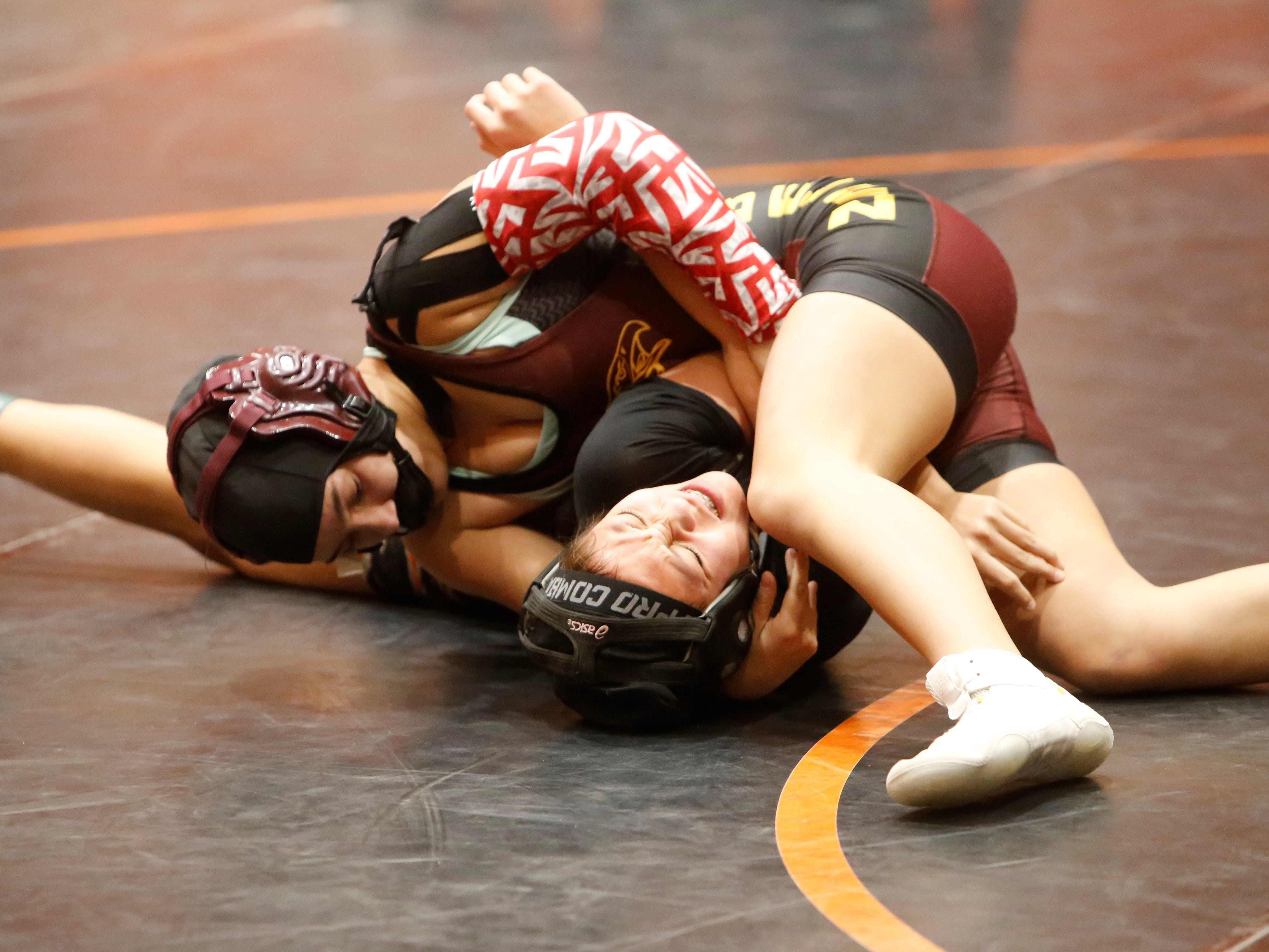 Belen's Cailean Romero spins around Gallup's Neveah Young during a 121-pound division match during Friday's first annual girls wrestling tournament in Aztec. Romero took third place in the 121-pound bracket.