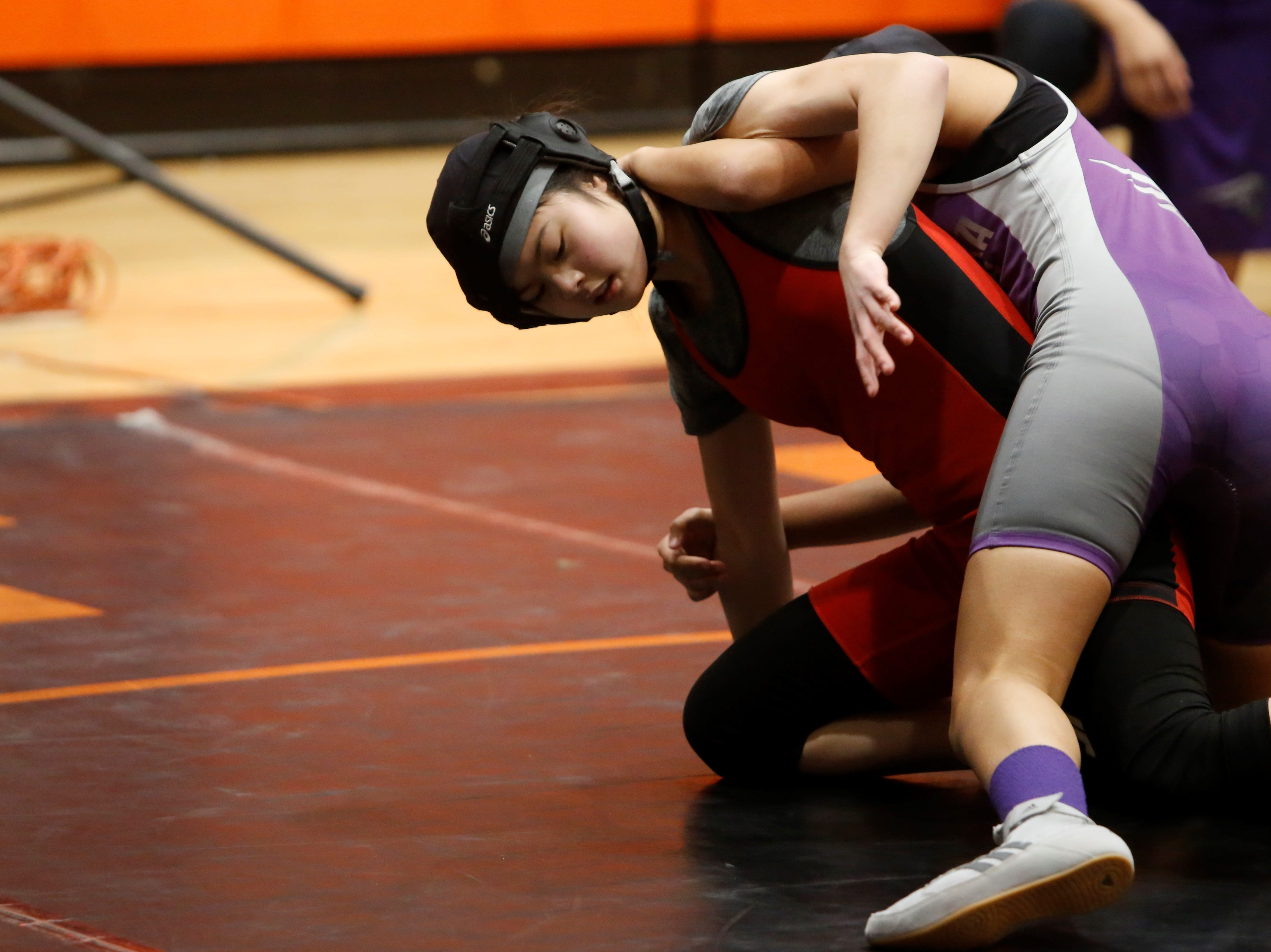 Albuquerque Academy's Sarah Wang tries to break free from Miyamura's Kaylen Leleiwi in a 110-pound division match during Friday's first annual girls wrestling tournament in Aztec. Leleiwi took first place, while Wang took second.
