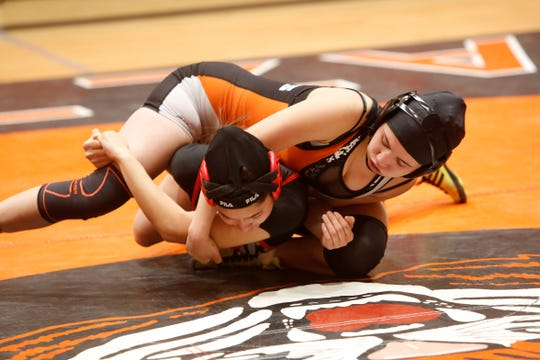 Aztec's Makayla Munoz locks up Albuquerque Academy's Melina Modisette during the 121-pound division championship match during Friday's first annual girls wrestling tournament in Aztec. Munoz won the match via 9-2 decision.