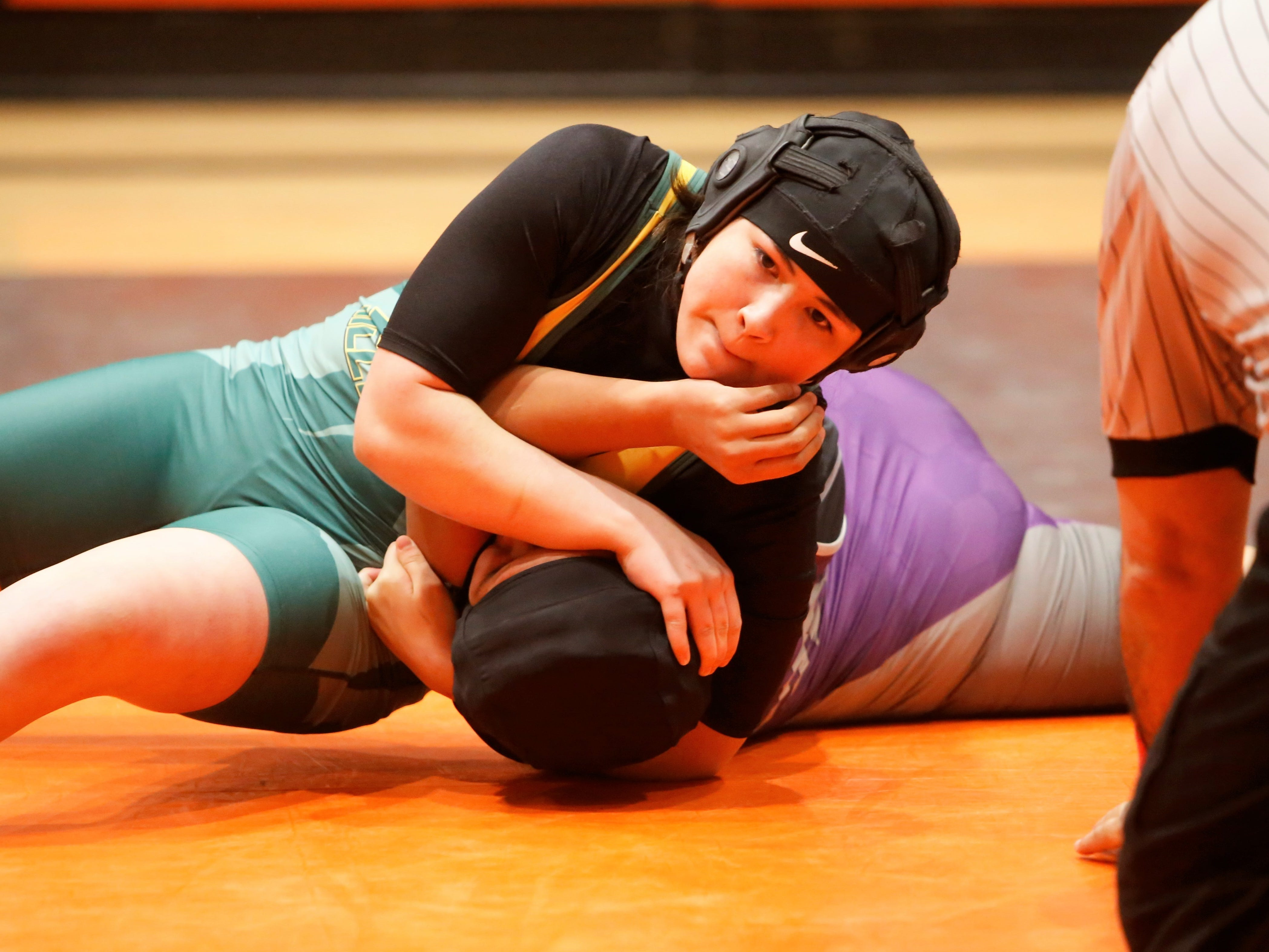 Los Alamos' Gloria Ramos pins Miyamura's Nizhoni Largo to the ground during a 143-pound division match during Friday's first annual girls wrestling tournament in Aztec. Ramos won the 143-pound division championship.
