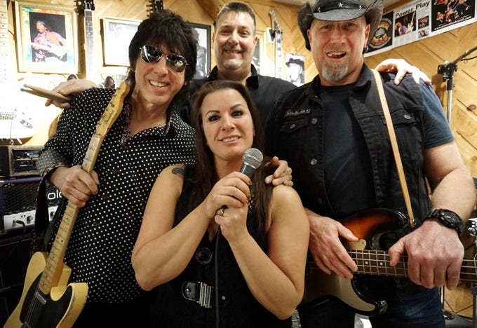 The members of Power Play gather in their Livonia garage-studio practice space on Jan. 25. From left is guitarist Michael Smith, singer April Hudson, drummer Bob Olds, and bassist Gary Kosten.