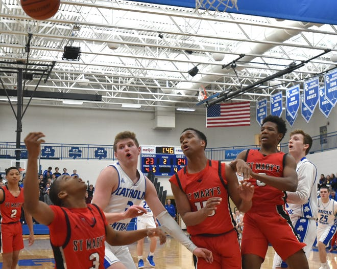 Players and a lone basketball go flying around near the baseline during Catholic Central and Orchard Lake St. Mary's Friday night game.
