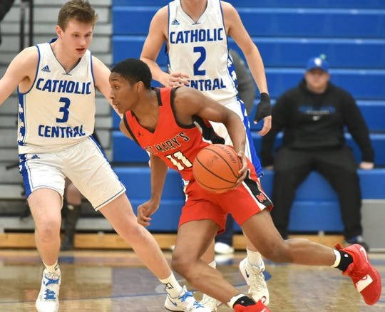 St. Mary Prep guard Lorne Bowman II dribbles at the top of the key guarded by Catholic Central's Davis Lukomski (3).