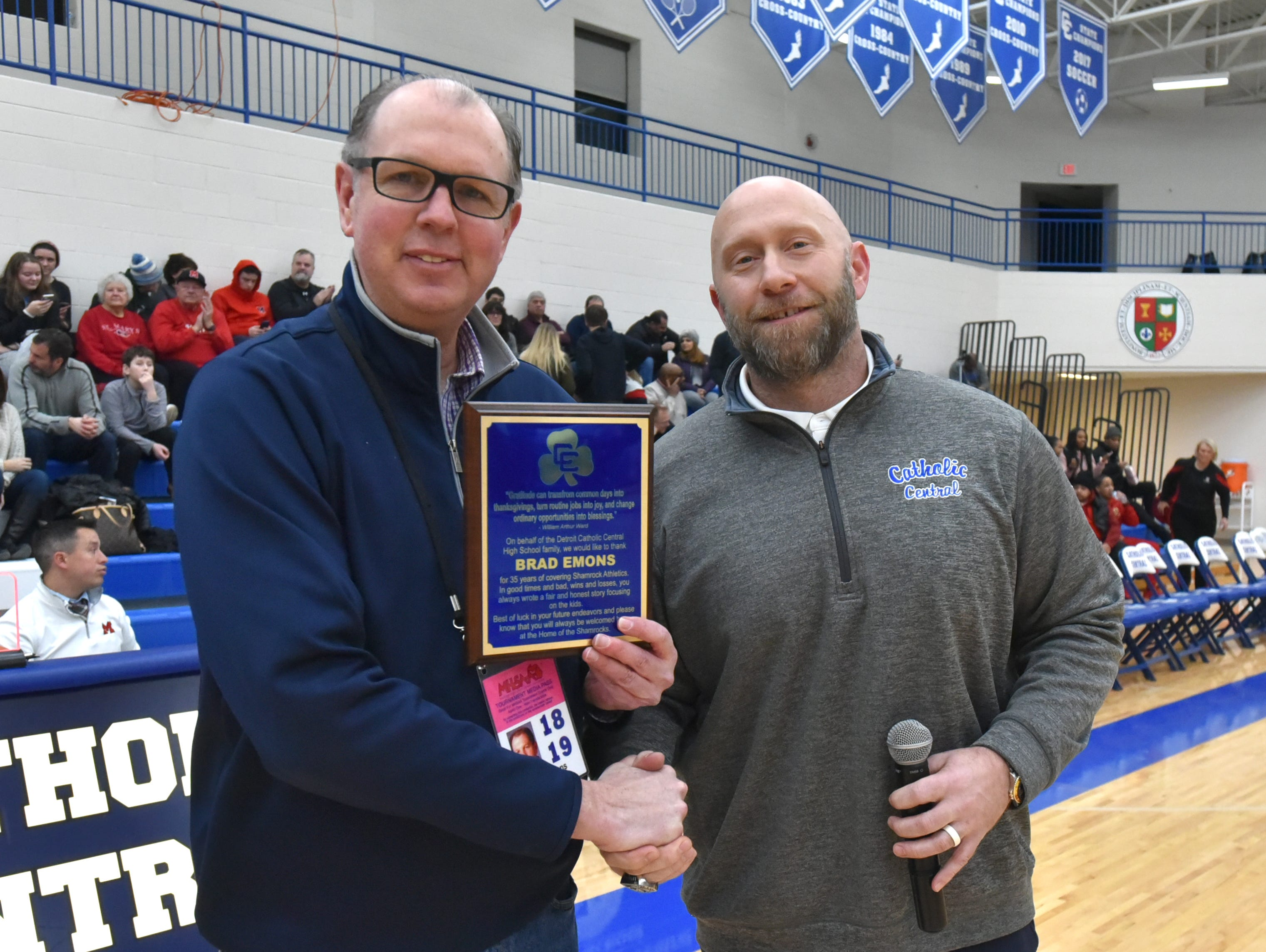 Detroit Catholic Central's Director of Athletics Aaron Babicz, right, honors Hometownlife.com sports reporter Brad Emons during halftime with a plaque commemorating his 35 years covering local high school sports and for his years of providing coverage of the Shamrocks when they were in Redford and Novi. Emons is retiring from the trade at the end of February.