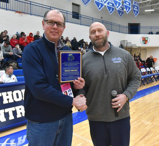 Detroit Catholic Central Director of Athletics Aaron Babicz (right) honors Hometownlife.com sports reporter Brad Emons during halftime with a plaque commemorating his 41 years covering local high school sports and for his years of providing coverage of the Shamrocks when they were in Redford and Novi.