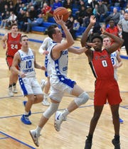 Brendan Downs begins to put a shot up against Orchard Lake St. Mary's Peter Nwoke - however Nwoke rose to the occasion and blocked Downs' shot.
