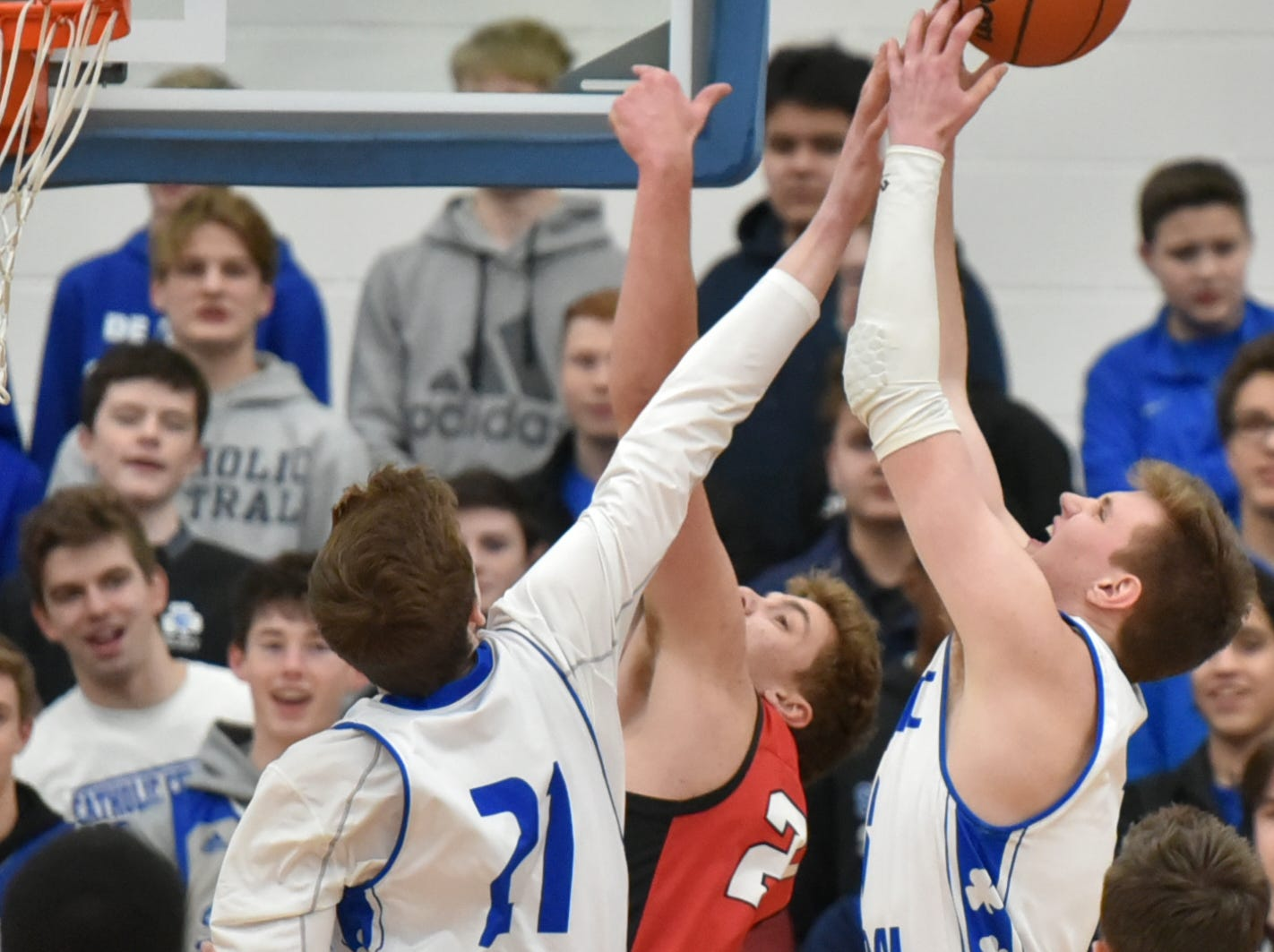 Detroit Catholic Central Shamrocks Justin Rukat, left, and Davis Lukomski, right, team up to give an Orchard Lake St. Mary's player some problems near the net during the teams' Jan. 25 game at CC's Novi campus.