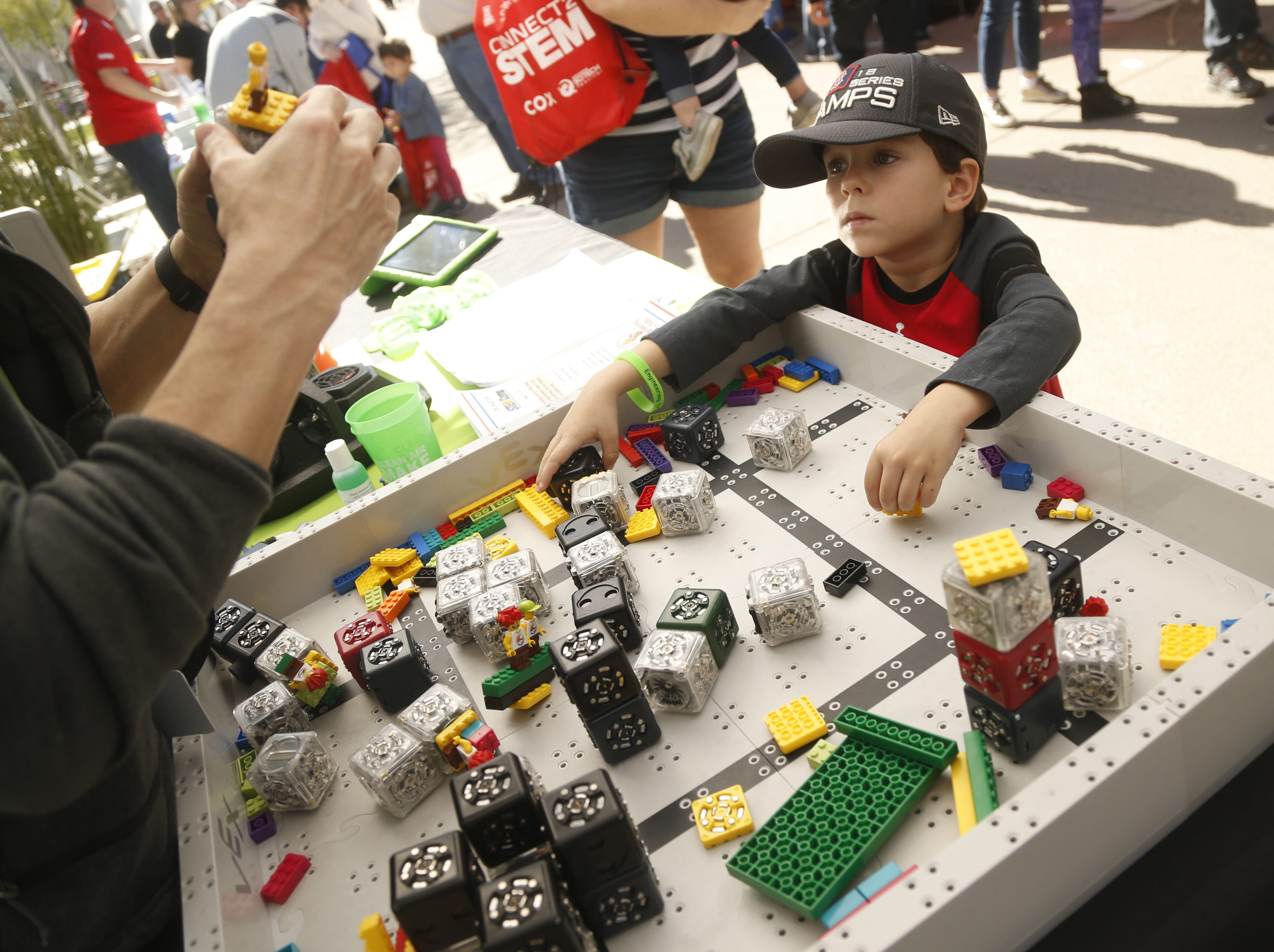 Gavin Desmarais, 4, watches as a LEGO robot is built during a STEM outreach event in downtown Phoenix, Ariz. on January 26, 2019.