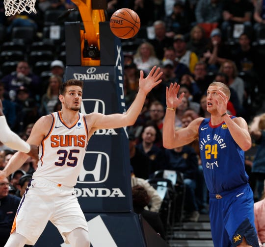 Phoenix Suns forward Dragan Bender, left, battles for control of the ball with Denver Nuggets forward Mason Plumlee in the first half of an NBA basketball game Friday, Jan. 25, 2019, in Denver. (AP Photo/David Zalubowski)