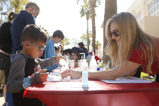Alex Stich (right) helps Andrew Gutierrez make hand sanitizer during a STEM outreach event in downtown Phoenix, Ariz. on January 26, 2019.