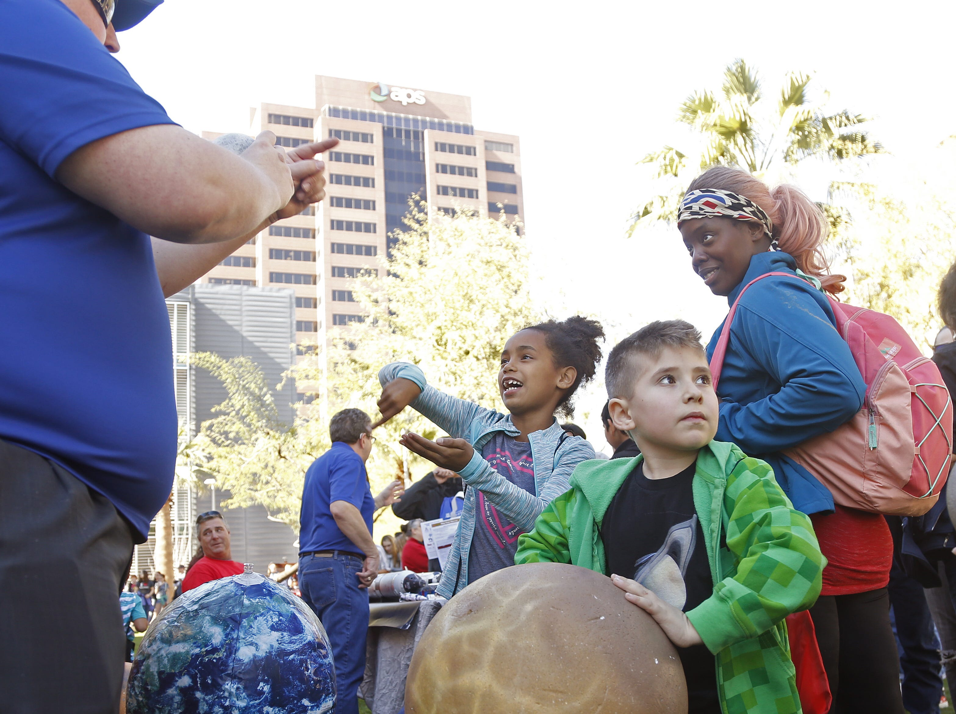Alexandra Swift talks with volunteer Taylor Shackelford (left) about the orbiting of the planets during a STEM outreach event in downtown Phoenix, Ariz. on January 26, 2019.