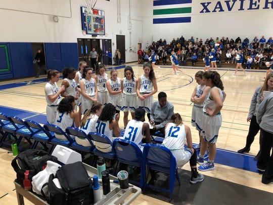 Xavier head coach Jennifer Gillom addresses her team against Perry.