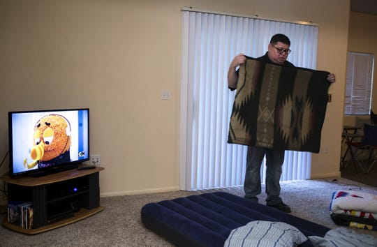 Jesse Bear Runner folds a blanket, January 24, 2019, in his Chandler apartment. Jesse and his children sleep on air mattresses in the living room.
