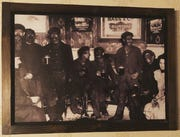 The photo of men covered in soot, drinking at a pub, framed on the wall of  a downtown Phoenix restaurant.
