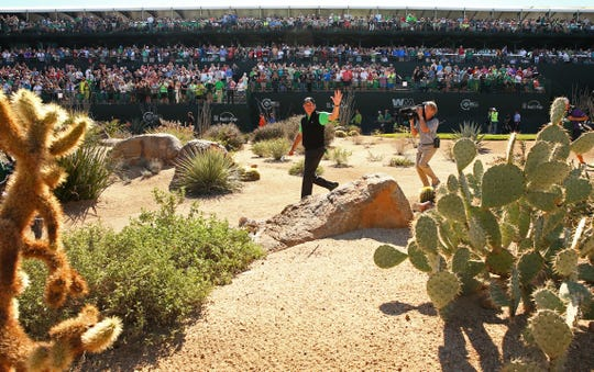 Phil Mickelson waves as the gallery gives him a standing ovation at the 16th green during round three at TPC Scottsdale on Feb. 4, 2017, at the Waste Management Phoenix Open.