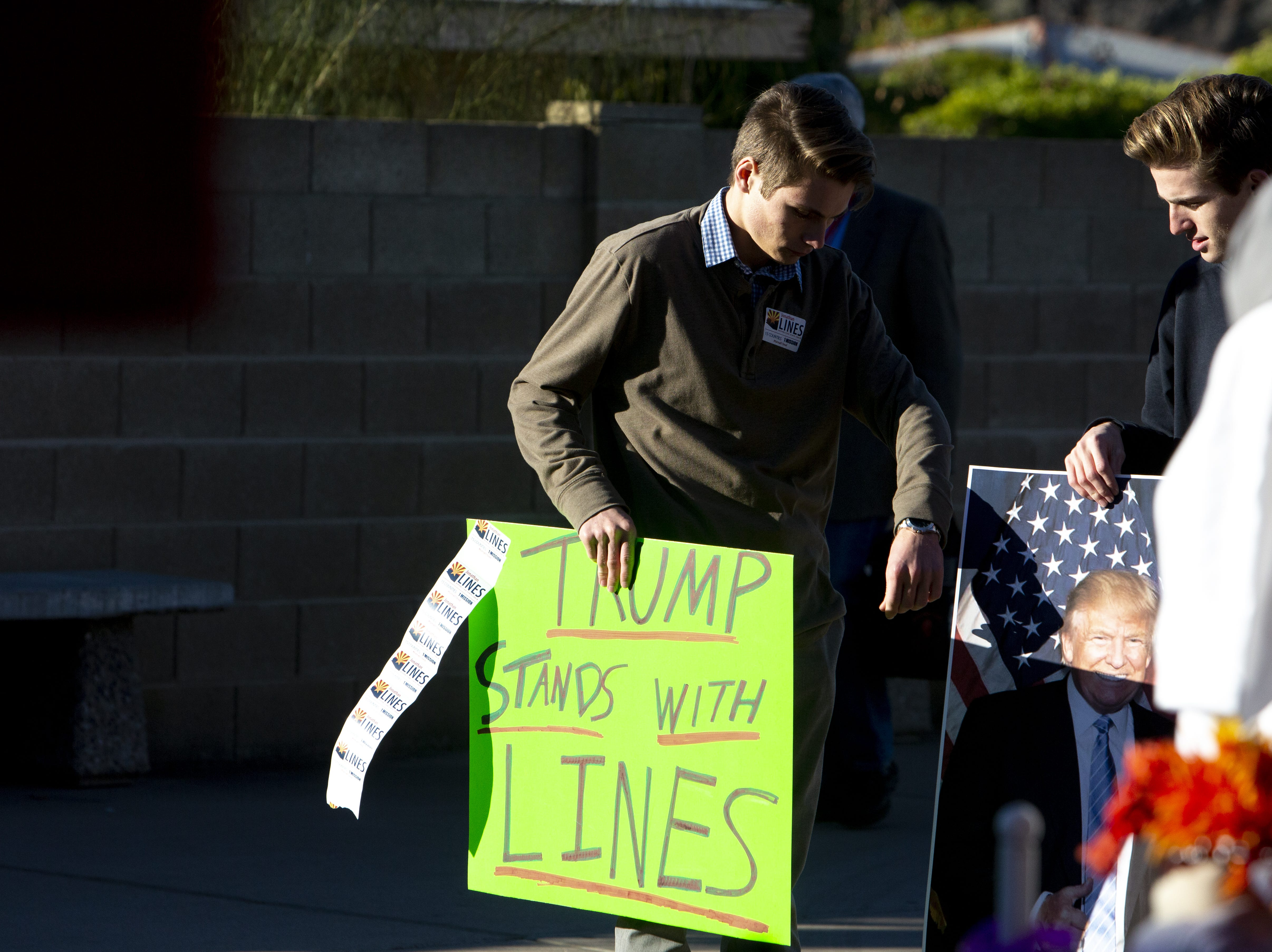 Teens hold signs supporting the current chairman of the Arizona Republican Party outside the Church for the Nations where the Statutory Meeting of the State Committee of the Arizona Republican Party was held on Saturday, Jan. 26, 2019.