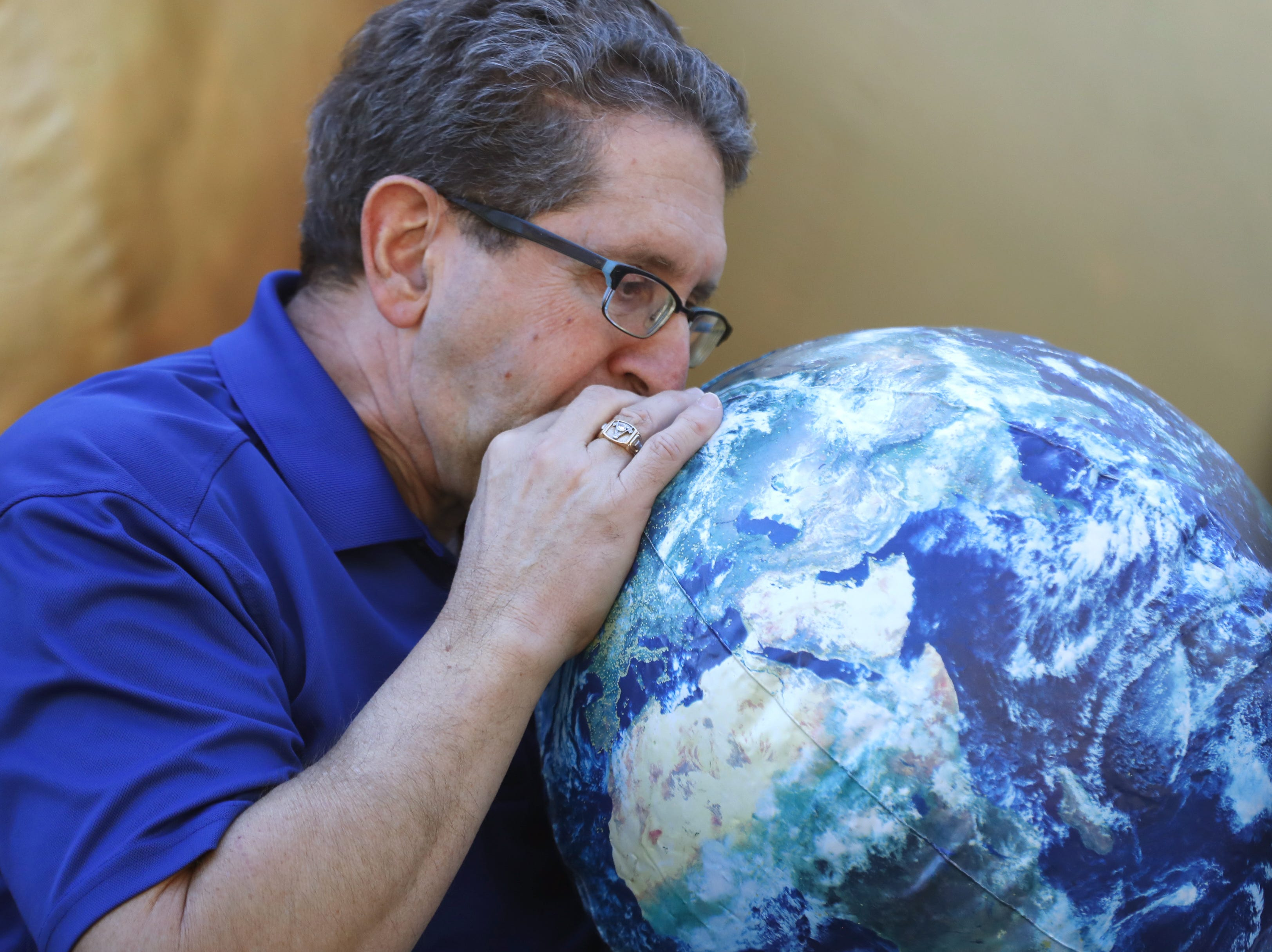 Gary Loeb, a volunteer docent, blows up a balloon Earth during a STEM outreach event in downtown Phoenix, Ariz. on January 26, 2019.