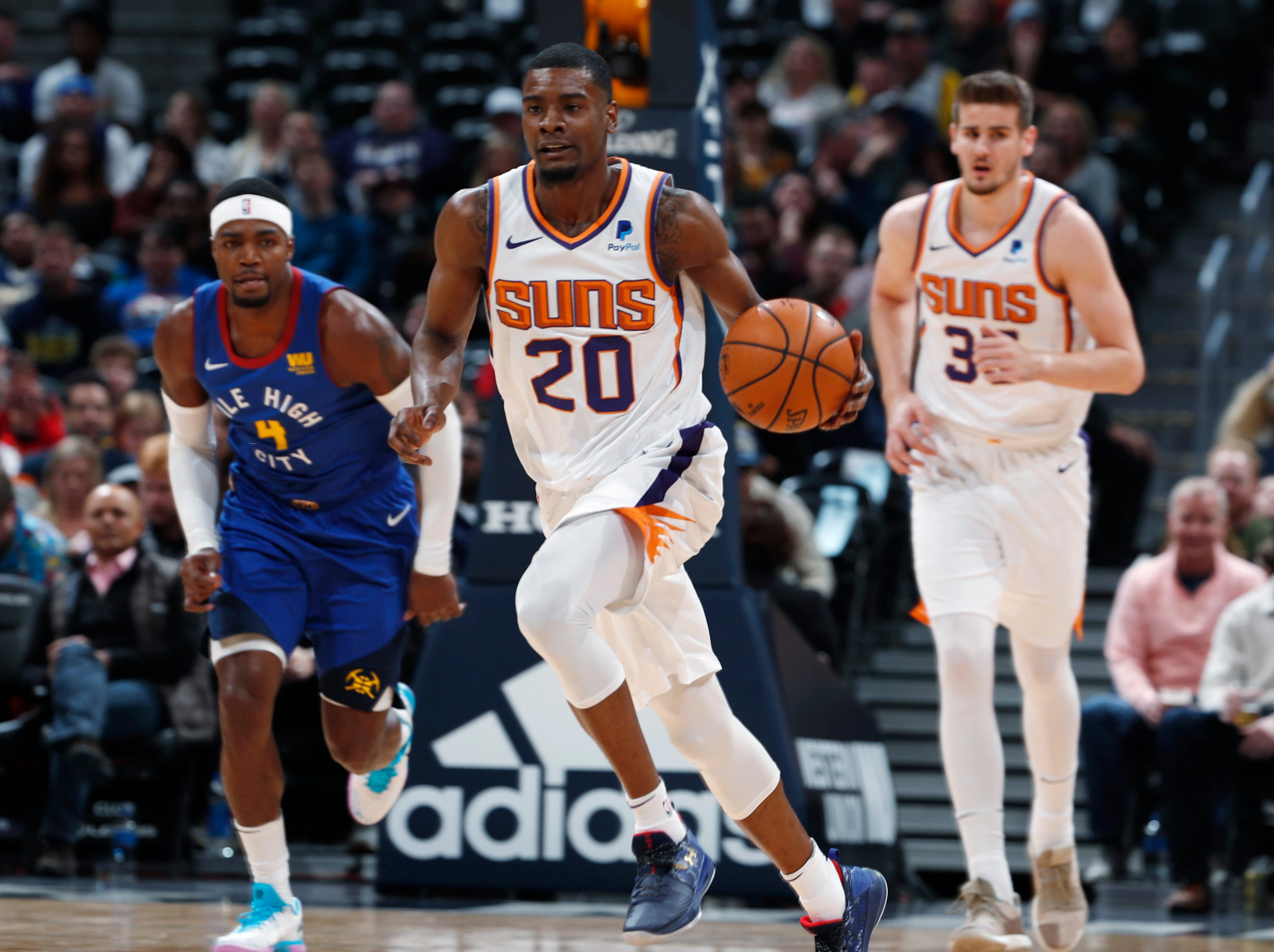 Phoenix Suns forward Josh Jackson, front, drives upcourt as Denver Nuggets forward Paul Millsap, back left, and Suns forward Dragan Bender follow in the first half of an NBA basketball game Friday, Jan. 25, 2019, in Denver. (AP Photo/David Zalubowski)