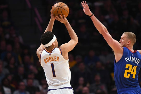 Jan 25, 2019; Denver, CO, USA; Phoenix Suns guard Devin Booker (1) shoots over Denver Nuggets forward Mason Plumlee (24) in the first quarter at the Pepsi Center. Mandatory Credit: Ron Chenoy-USA TODAY Sports