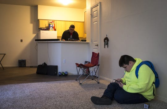 Jesse Bear Runner Jr. waits to leave for school, while his dad, Jesse Bear Runner cleans the kitchen, January 24, 2019, in their Chandler apartment.