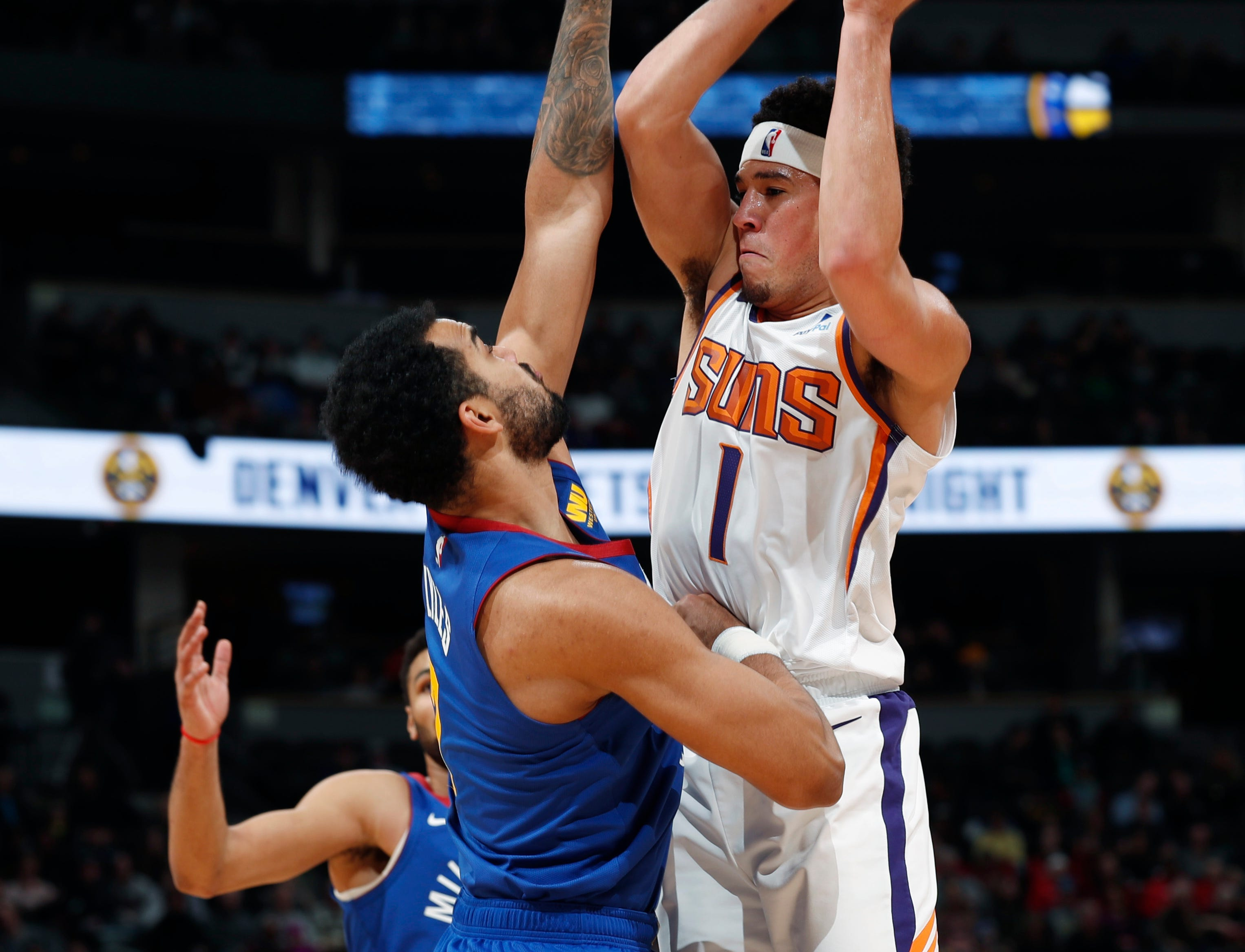 Phoenix Suns guard Devin Booker, right, goes up to shoot as Denver Nuggets forward Trey Lyles defends in the first half of an NBA basketball game Friday, Jan. 25, 2019, in Denver. (AP Photo/David Zalubowski)