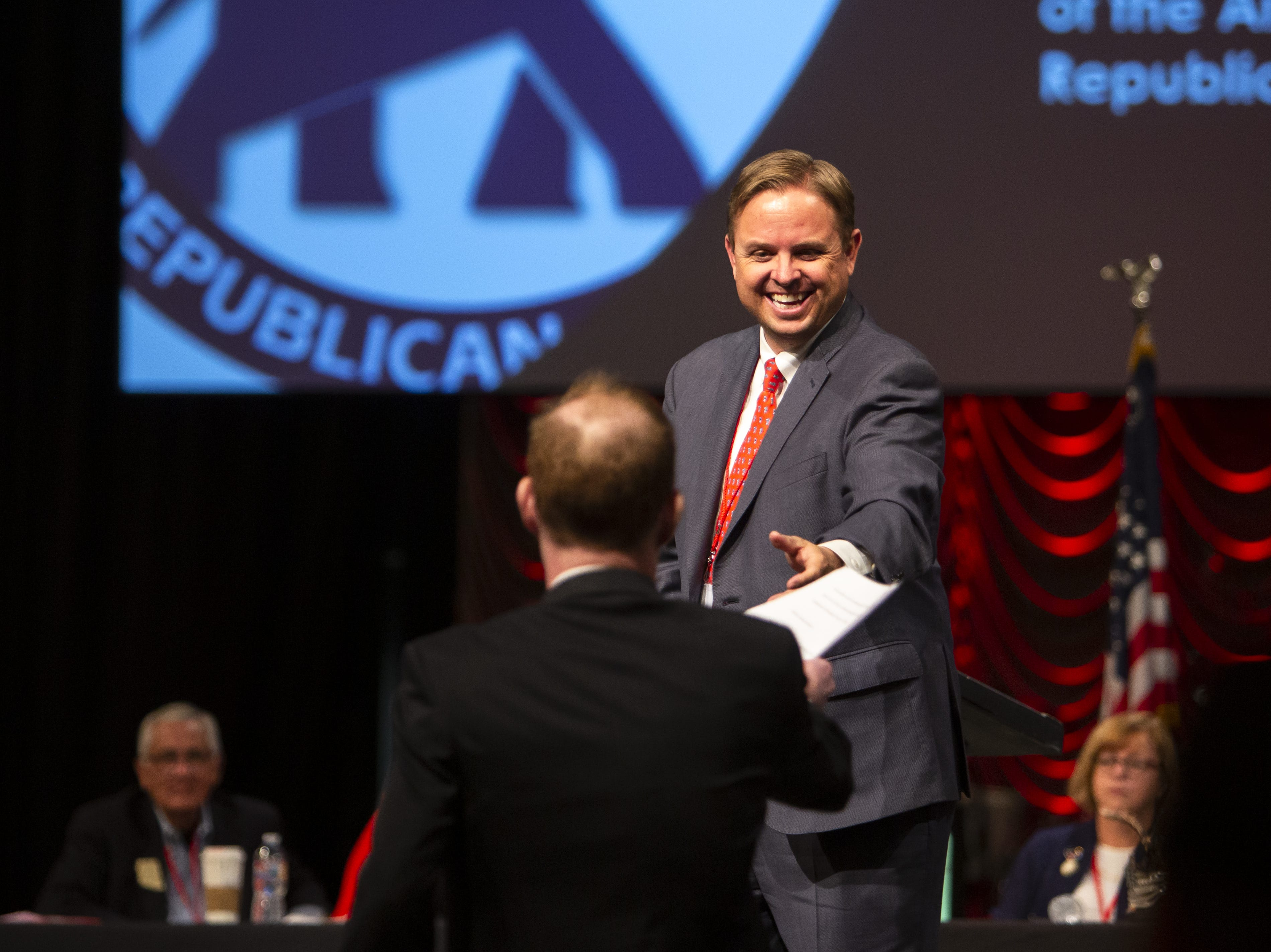 Lawyer Stephen Richer hands papers to Jonathan Lines during the Statutory Meeting of the State Committee of the Arizona Republican Party at Church for the Nations on Saturday, Jan. 26, 2019.