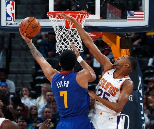 Phoenix Suns forward Mikal Bridges, right, blocks a shot by Denver Nuggets forward Trey Lyles in the first half of an NBA basketball game Friday, Jan. 25, 2019, in Denver. (AP Photo/David Zalubowski)