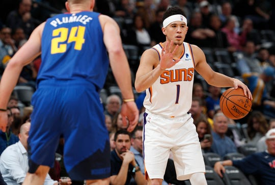 Phoenix Suns guard Devin Booker, back, looks to pass the ball as Denver Nuggets forward Mason Plumlee defends in the first half of an NBA basketball game Friday, Jan. 25, 2019, in Denver. (AP Photo/David Zalubowski)