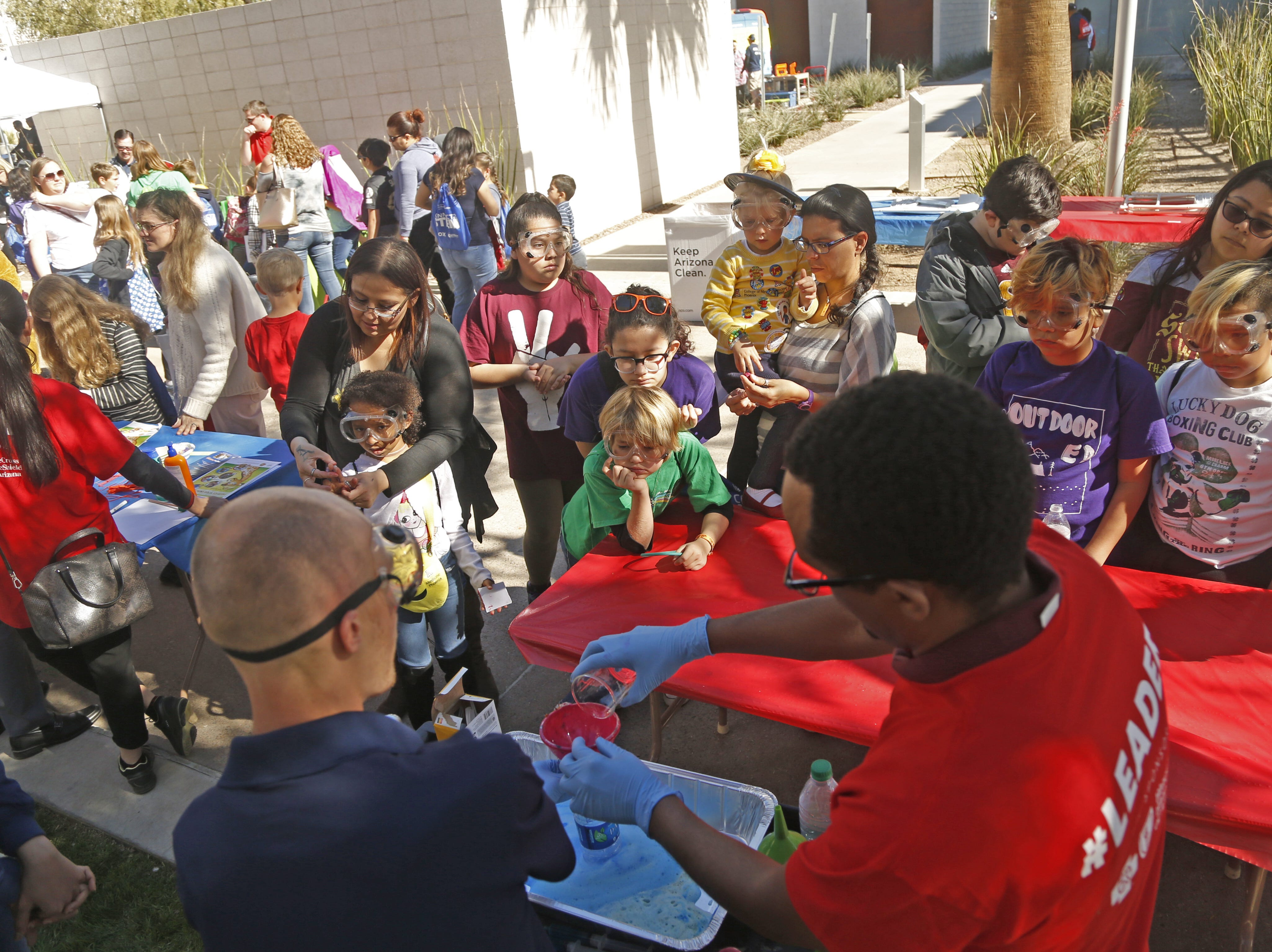 Children look at experiments watching for the chemical reaction during a STEM outreach event in downtown Phoenix, Ariz. on January 26, 2019.