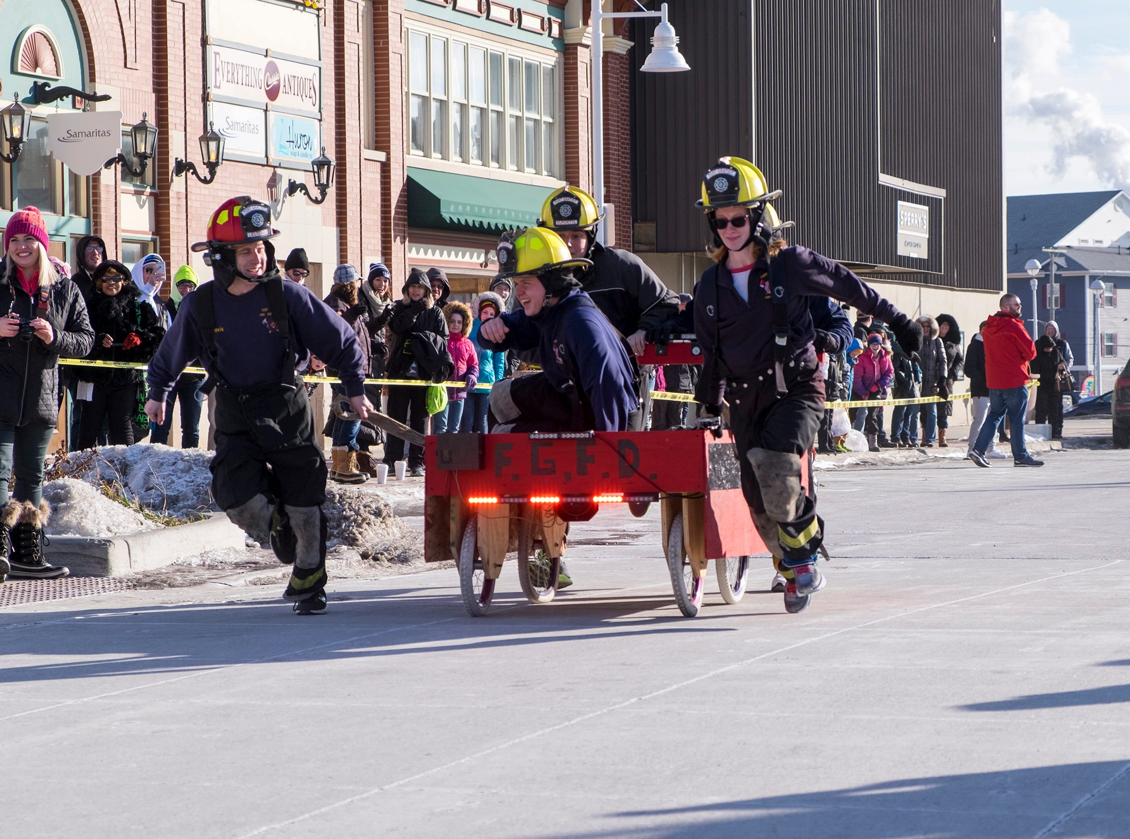 Fort Gratiot Fire Department team members pull their bed down Superior Mall Saturday, Jan. 26, 2019 during the annual Port Huron Chilly Fest bed races.
