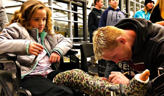Lock Haven's Chance Marsteller, right, autographs a cast for Kaiya Wilkins, 8, of West York Borough, following NCAA Division I wrestling wrestling action at Red Lion Area High School in Red Lion, Friday, Jan. 25, 2019. Dawn J. Sagert photo