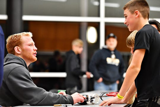 Lock Haven's Chance Marsteller, left, autographs head gear for David Rentzel, 13, of Windsor following NCAA Division I wrestling wrestling action at Red Lion Area High School in Red Lion, Friday, Jan. 25, 2019. Dawn J. Sagert photo