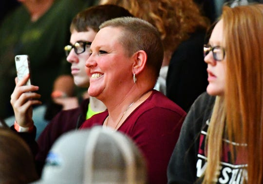 From front, Kylie Marsteller, 16, and Suzanne Marsteller, both of Fawn Township, and Jon Thomassy, 14, of West Manchester, look on as Lock Haven's Chance Marsteller wrestles Arizona State's Josh Shields in the 165-pound weight class during NCAA Division I wrestling wrestling action at Red Lion Area High School in Red Lion, Friday, Jan. 25.