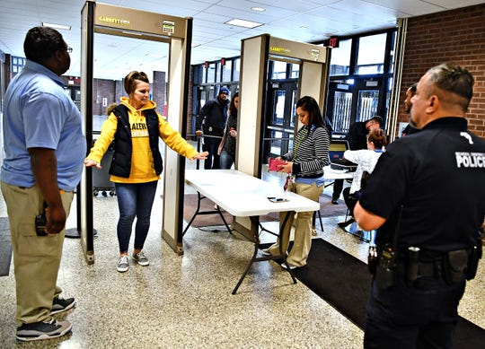 """From left, York High Hall Monitor Kelvin Harrison, left, stands by as Coleen Hurst, of Lancaster City, passes through the metal detector and York City School Police Officer Ori Rivera, right, looks on while screening attendants as they arrive for the girls' basketball games at the school in York City, Saturday, Jan. 26, 2019. Because of """"safety and security concerns,"""" the boys games against Chester, that were also scheduled for Saturday, have been postponed. Dawn J. Sagert photo"""