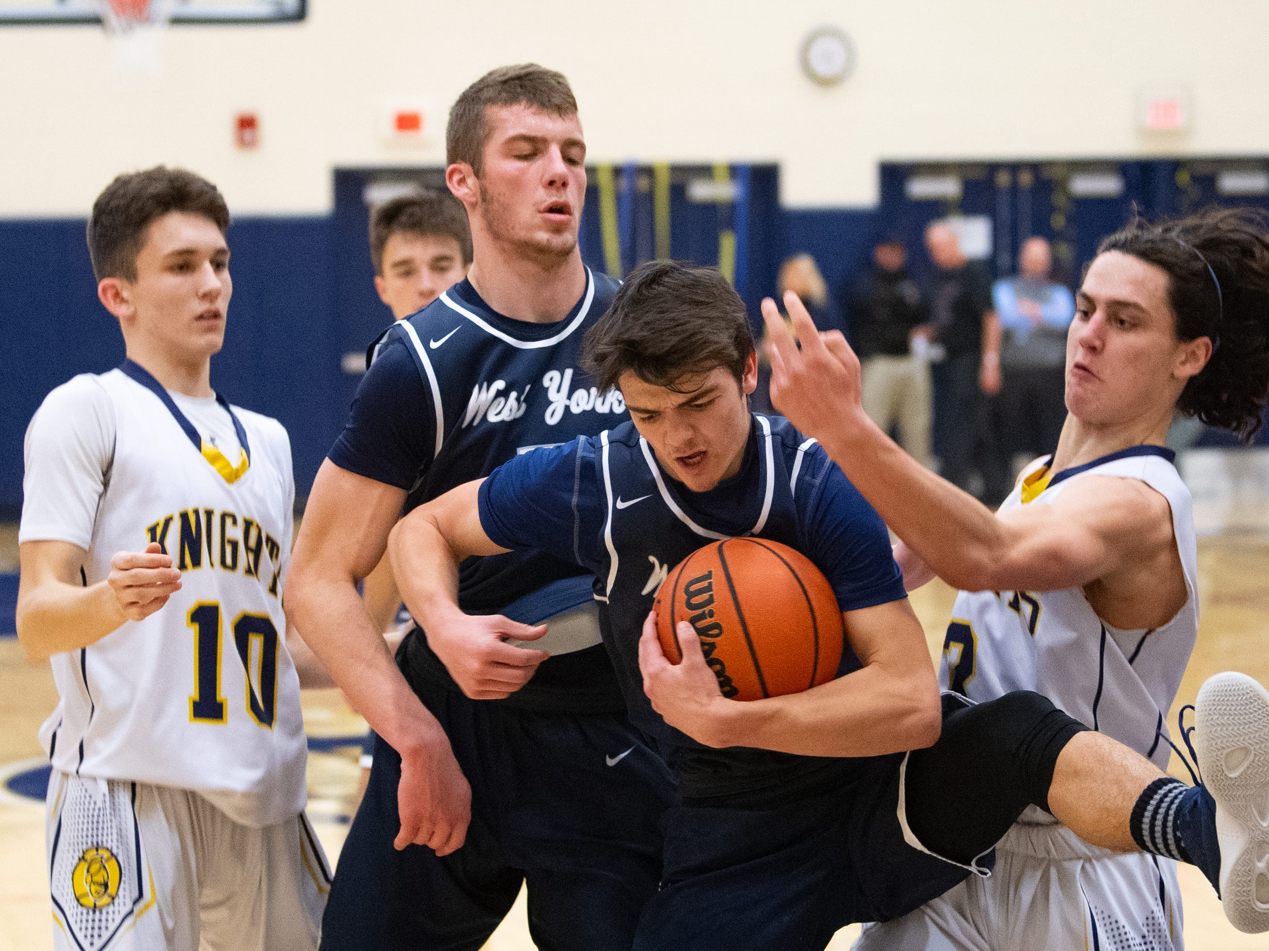 Jared Shearer (21) pulls down the rebound during the YAIAA boys' basketball game between Eastern York and West York, Friday, January 25, 2019. The Golden Knights defeated the Bulldogs 59 to 55.