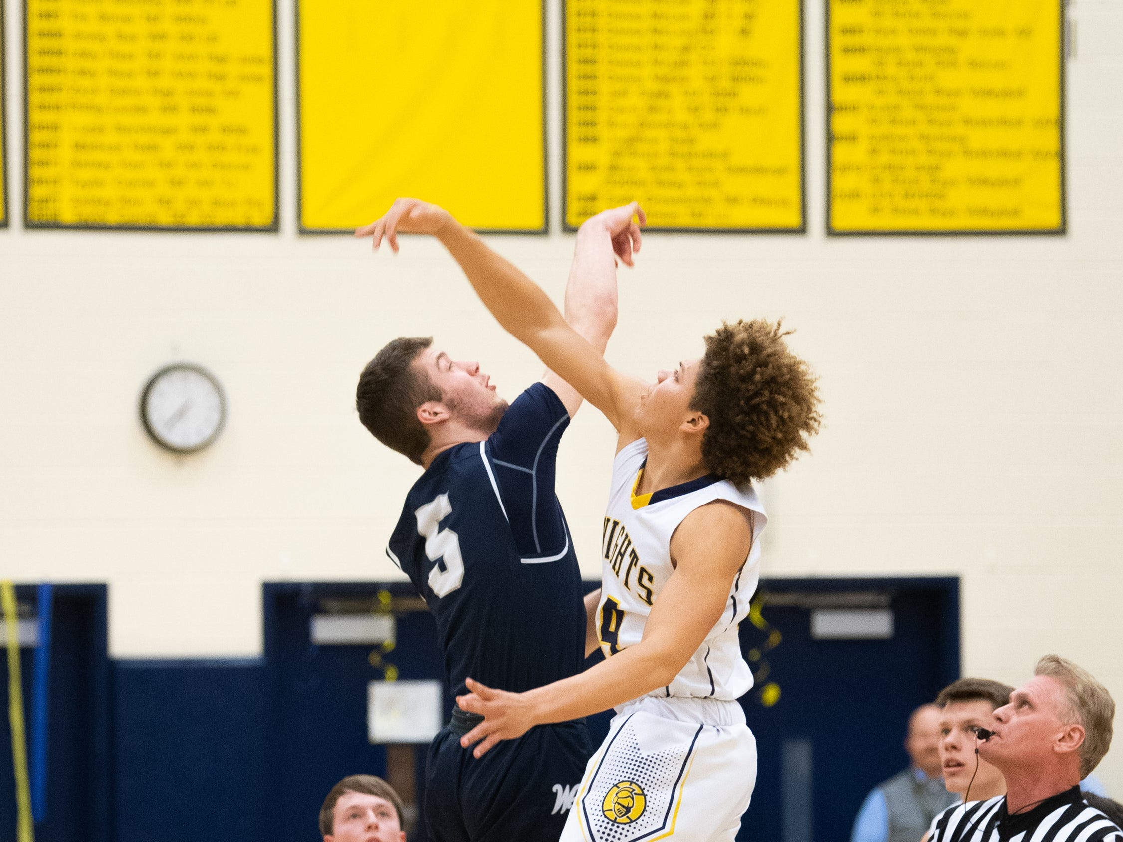 Andrew LaManna (5) and DeMonte Martin (14) go for the opening tip-off during the YAIAA boys' basketball game between Eastern York and West York, Friday, January 25, 2019 at Eastern York High School. The Golden Knights defeated the Bulldogs 59 to 55.