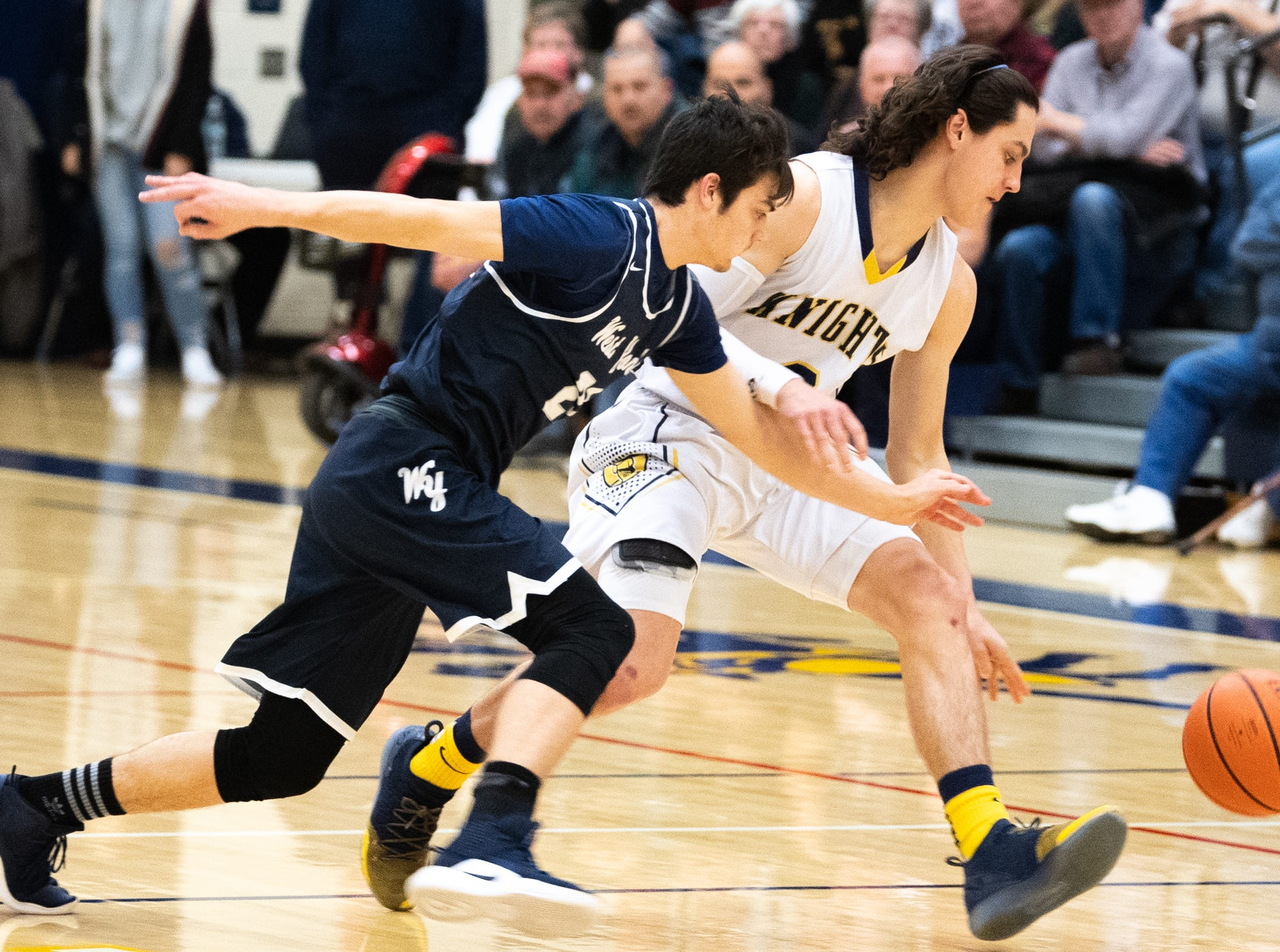 Jared Shearer (21) of West York looks to steal the ball from Eastern York's Bryce Henise (2) during the YAIAA boys' basketball game, Friday, January 25, 2019. The Golden Knights defeated the Bulldogs 59 to 55.